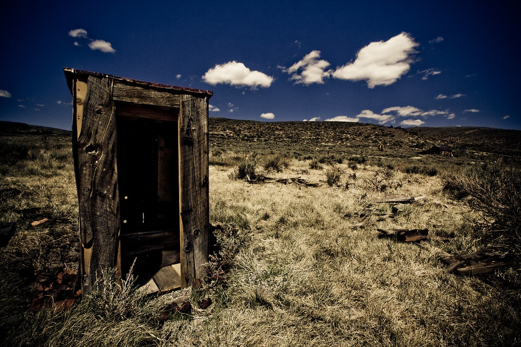 A wooden outhouse sits in the left corner of a desert scene with blue sky and sage brush
