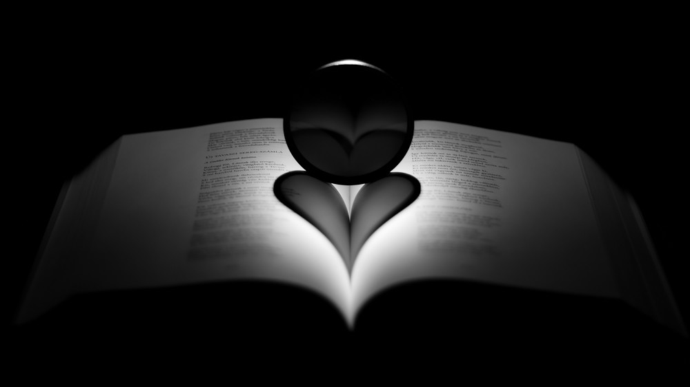 A black glass orb sits in drastic lighting on the pages of a book, casting the shadow of a dark heart on its pages.