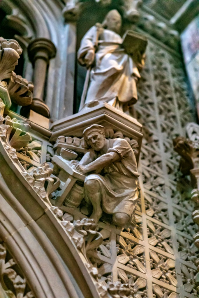 """The frieze on a cathedral in Scotland shows a priestly figure standing on a platform that rests on the back of a worker below. """"Social hierarchy"""" by schoeband is licensed under CC BY-NC-ND 2.0"""