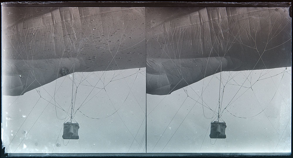A black and white stereoscopic card of a WWI-era observation balloon - a small basket with a single person visible inside in dangles precariously from a hot air balloon