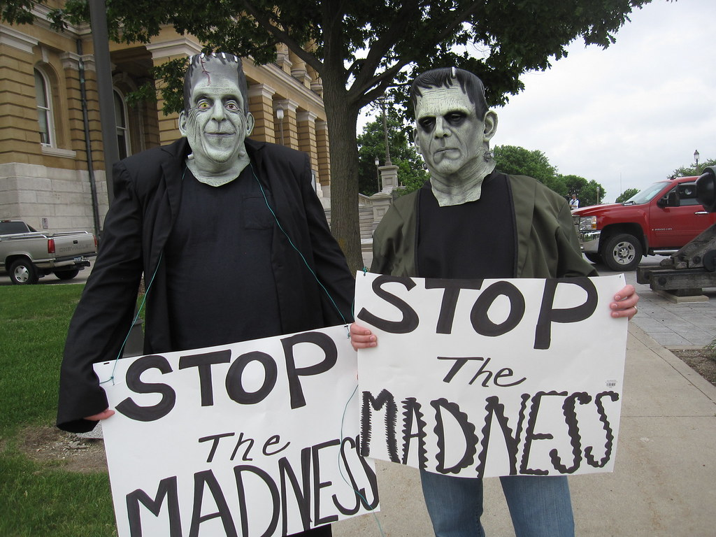 """Two people in Frankenstein masks stand in front of an Iowa courthouse, holding signs that read """"Stop the Madness."""""""